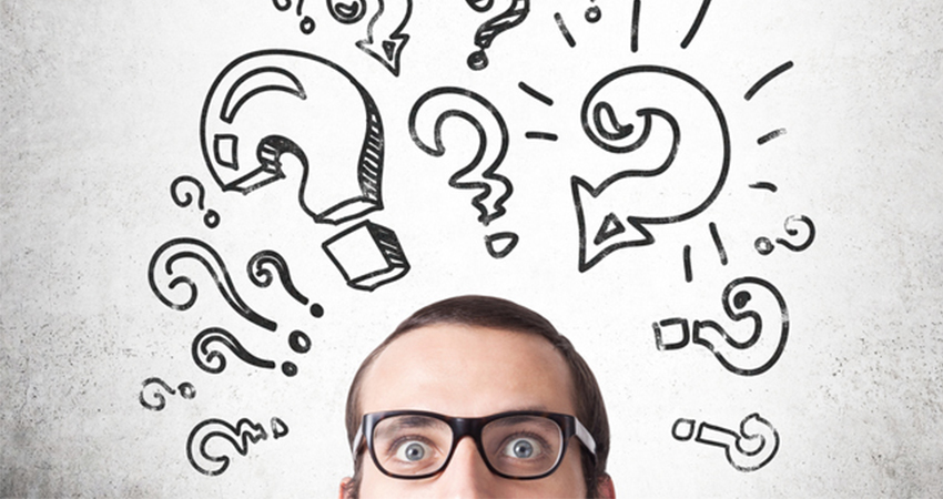 Man with glasses surrounded by questions mark symbols
